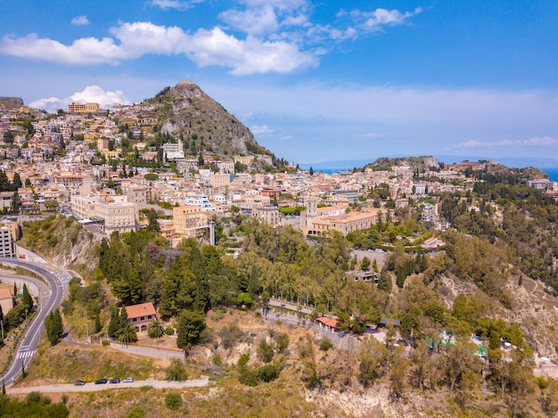 Aerial shot of buildings surrounded by trees in taormina sicily, italy