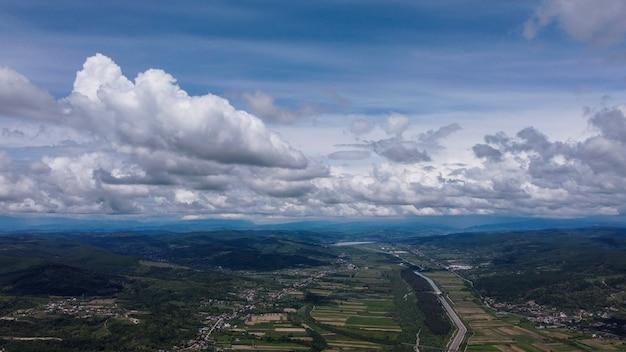 Ripresa aerea di edifici con campi e montagne sotto il cielo nuvoloso