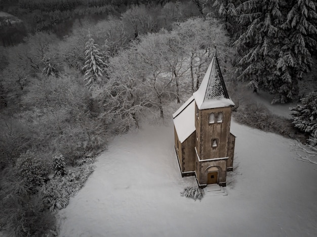 Aerial shot of a church covered in the snow surrounded by leafless trees