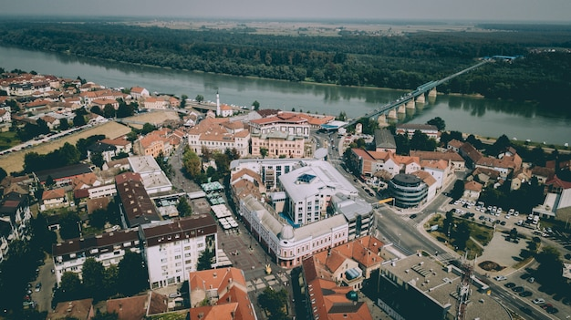 Aerial shot of city buildings with a bridge over the river near trees and plants