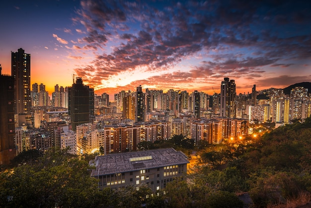 Aerial shot of city skyline under an orange sky at sunset
