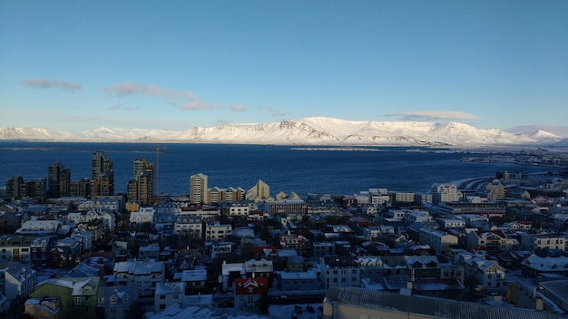 Aerial shot of the coastal city of reykjavik with snow covered mountains against a blue sky