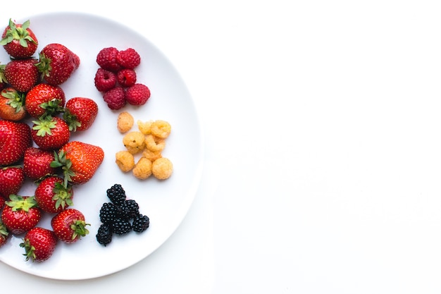 Aerial shot of colorful healthy fresh berries on a plate on a white background