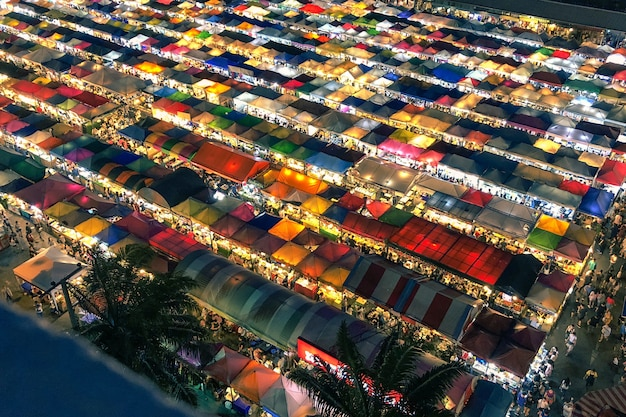 Aerial shot of colorful market tents with lit lights at night time
