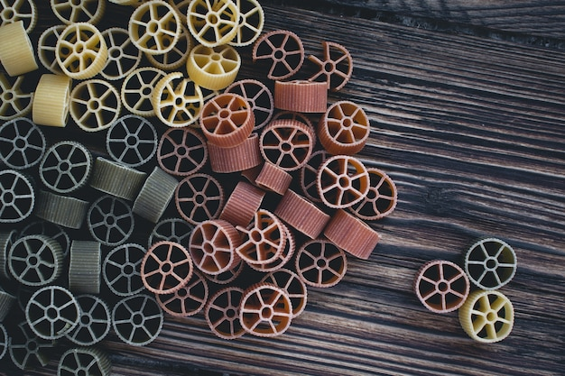 Aerial shot of colorful wheel pasta on a wooden background