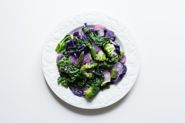 Aerial shot of cooked vibrant spring seasonal vegetables on a white background