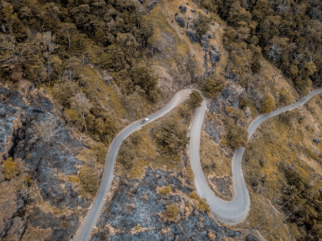 Aerial shot of a curvy road on the mountains with trees
