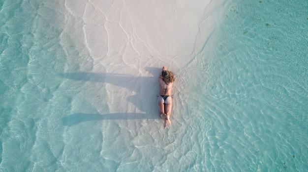 Ripresa aerea di una ragazza in posa sulla sabbia e abbronzatura in spiaggia