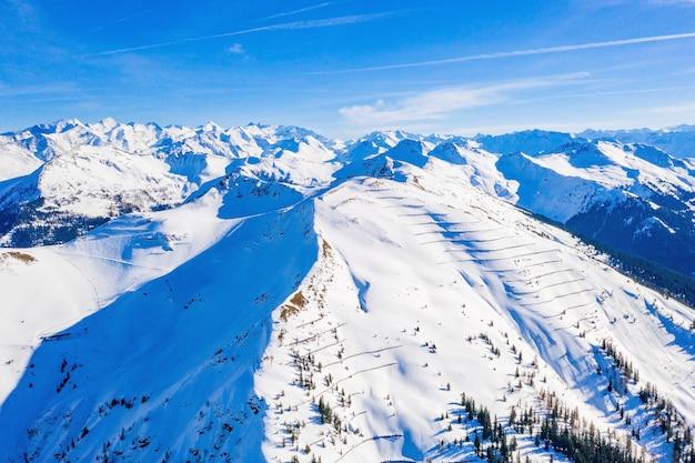 Ripresa aerea di alte montagne innevate in austria in una giornata di sole Foto Gratuite