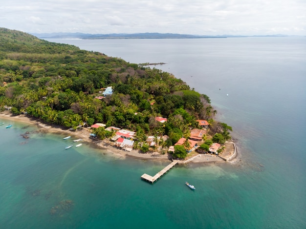 Aerial shot of an island with a few house on the shore and a forest