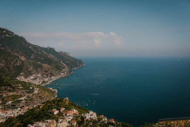 Aerial shot of a landscape with buildings on the coast of the sea in italy