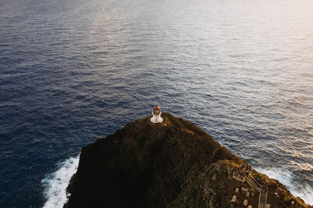 Aerial shot of a lighthouse at the top of the cliff in the open sea