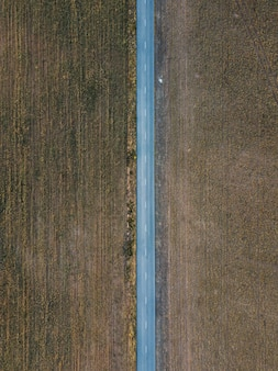 Aerial shot of the long highway surrounded by fields in portugal