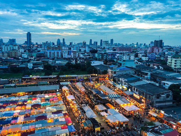 Aerial shot of market tents near buildings under a blue sky