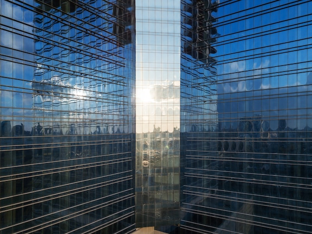 Aerial shot of modern office building windows, reflection of cityscape on a sunny day.