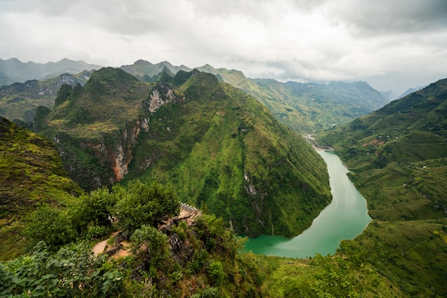Aerial shot of a narrow river in the mountains under the cloudy sky in vietnam