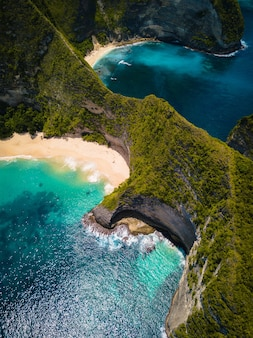 Aerial shot of the ocean  surrounded by beautiful cliffs covered in greens