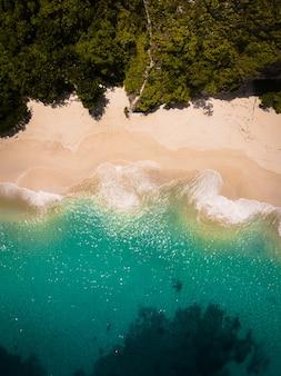 Ripresa aerea delle onde dell'oceano che colpiscono la spiaggia sabbiosa