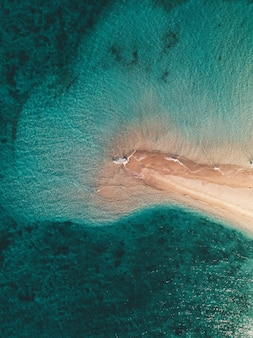 Aerial shot of the ocean waves hitting the small sandy island