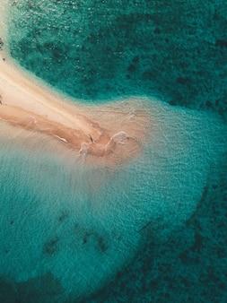 Ripresa aerea delle onde dell'oceano che colpiscono la piccola isola sabbiosa