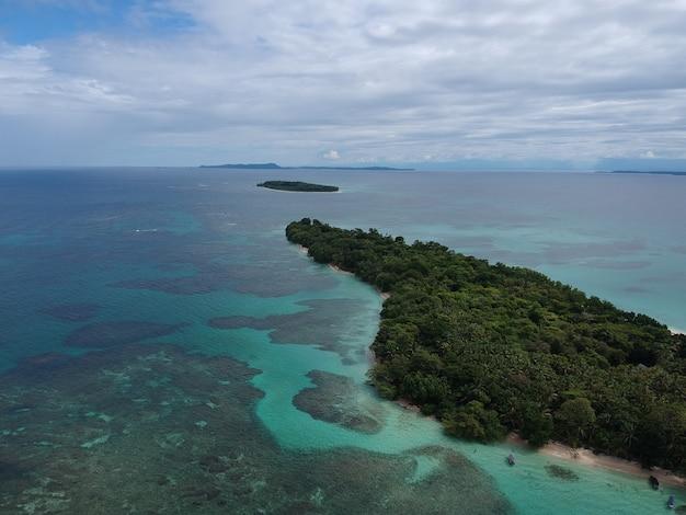 나무로 덮이고 청록색 물로 둘러싸인 아름다운 섬의 항공 샷