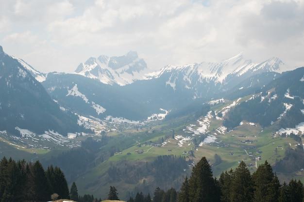 흐린 하늘 아래 눈으로 덮여 아름다운 산맥의 공중 촬영