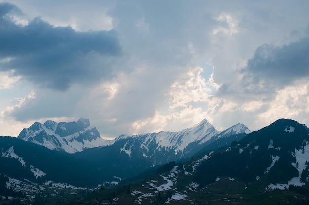 曇り空の下で雪に覆われた美しい山脈の空中ショット