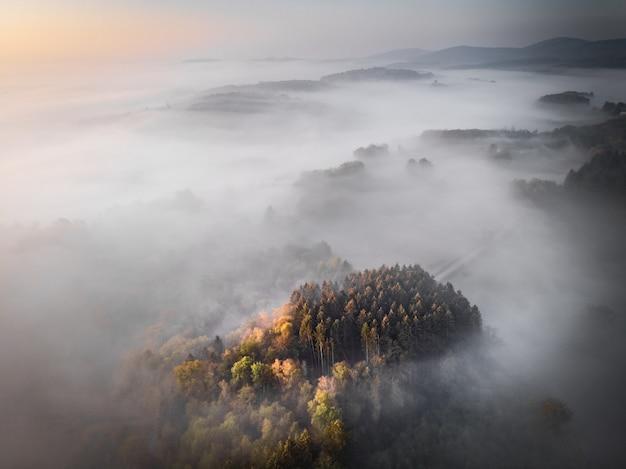 Воздушная съемка покрытой лесом горы, поросшей туманом, фоном великолепных форумов или блогом