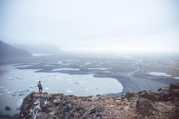 アイスランドで撮影された霧の中で湖を見下ろす崖の上に立っている人の空中ショット