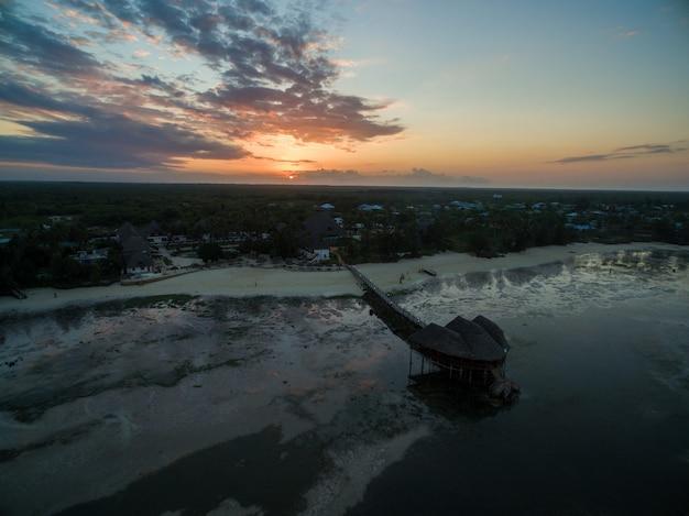 ザンジバル、アフリカの夕日の下でキャプチャされた海沿いのビーチで桟橋の空中ショット
