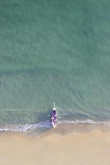 햇빛 아래 아름다운 해안에 보라색 보트의 공중 촬영