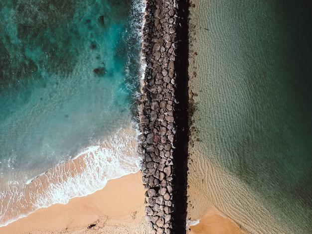 昼間の海の岩だらけの小道の空中ショット