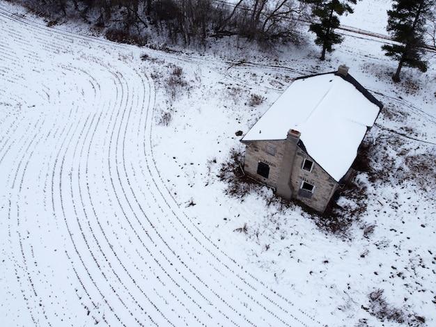 雪に覆われた畑のある田舎の家の空中ショット