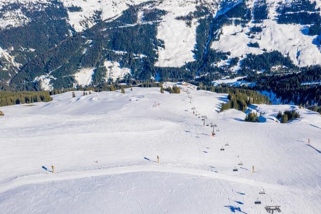 Воздушный снимок горнолыжного курорта на заснеженной горе при дневном свете