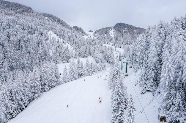 日光の下で雪景色のスキーコースの空中ショット