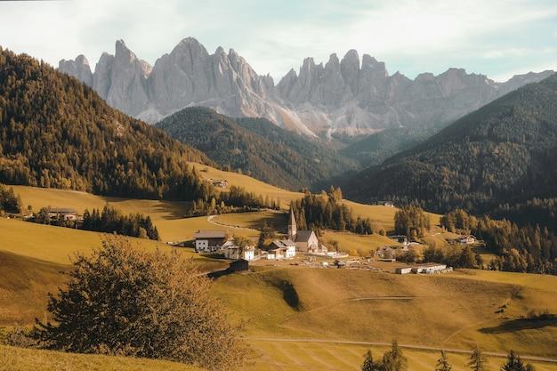 昼間の森林に覆われた山々に囲まれた乾いた草が茂った丘の上の村の空中ショット