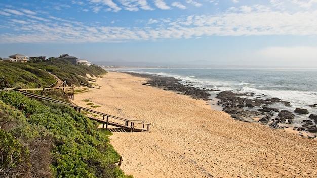 息をのむような海沿いのビーチに来る木製の小道の空中ショット