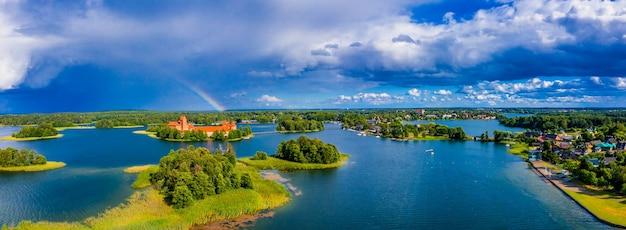 緑の森と古い城のある島に囲まれた素晴らしい湖の空中ショット