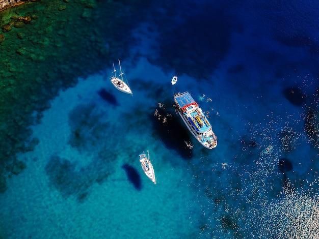 Воздушная выстрел из красивой голубой лагуны в жаркий летний день с парусной лодке. вид сверху людей плавают вокруг лодки.