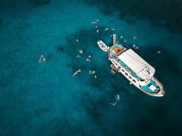 Воздушная выстрел из красивой голубой лагуны в жаркий летний день с парусной лодке. вид сверху людей, плавающих вокруг лодки.