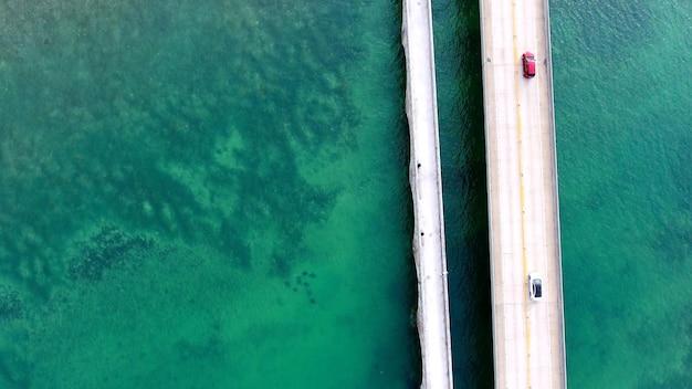 フロリダの海に架かる橋の上を運転する車の空中ショット