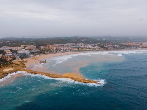 砂浜の海岸に当たる泡の波の空中ショット