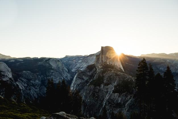 昼間の太陽光線と灰色と黒のロッキー山脈の空中ショット