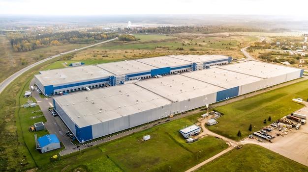 産業倉庫の空中ショットローディングハブと貨物トレーラー付きの多くのトラック