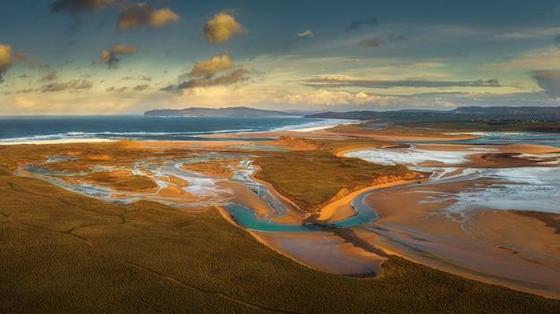 일몰 오렌지 하늘 아래 바다로 둘러싸인 땅의 공중 촬영