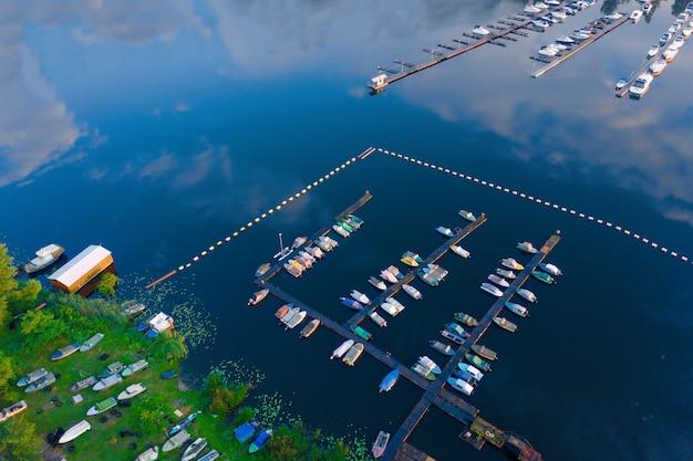 日当たりの良い夏の朝の雲の反射と青い水の中の桟橋に多くのボートが偶数列に係留されたマリーナの空中ショット。