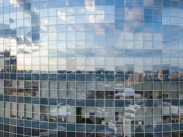 現代のオフィスビルの窓の空中ショット、ウクライナのキエフの晴れた日の街並みの反射。