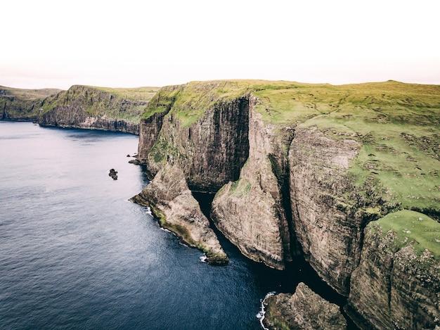 거대한 절벽과 녹색 필드가있는 바다와 해안의 공중 샷
