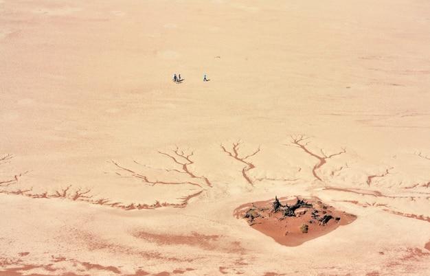 昼間に割れた砂漠の地面の近くに立っている人の空中ショット