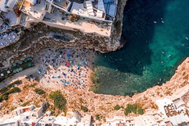 日光の下で崖に囲まれたアドリア海で泳ぐ人々の空中ショット